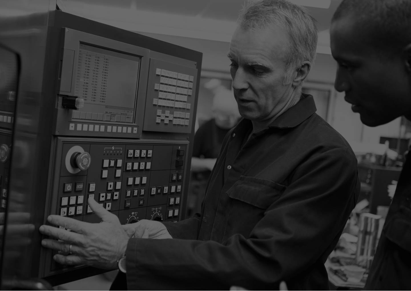 Close Up Of Engineer training someone to use a machine